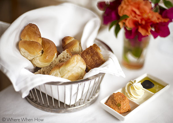 A photograph of Warm breads and crusty rolls served with various butter spreads. Grace's Cottage, Grace Bay, Providenciales (Provo), Turks and Caicos Islands.
