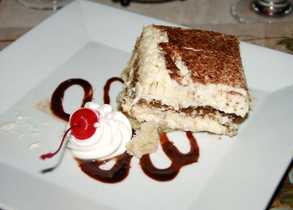 A photograph of Smooth and creamy Tiramisu with a cherry at Las Brisas Restaurant, Chalk Sound, Providenciales (Provo), Turks and Caicos Islands.