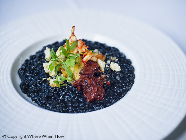 A photograph of Squid Ink Arborio, Caicos Lobster Tail with Puttanesca Sauce Risotto, Providenciales (Provo), Turks and Caicos Islands.