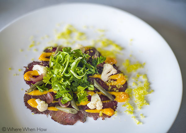 A photograph of Beef Tenderloin Carpaccio is served with thin focaccia toasts at The Somerset, Grace Bay, Providenciales (Provo), Turks and Caicos Islands.